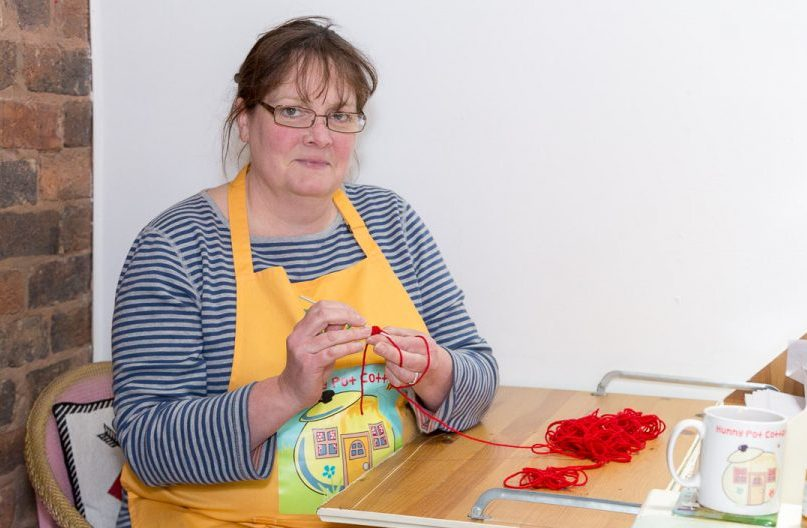 Ruth crochets at her desk